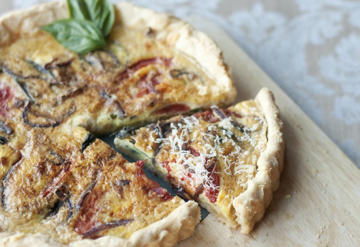 Golden,Crusted,Quiche,With,Heirloom,Tomatoes,,Onions,And,Herbs