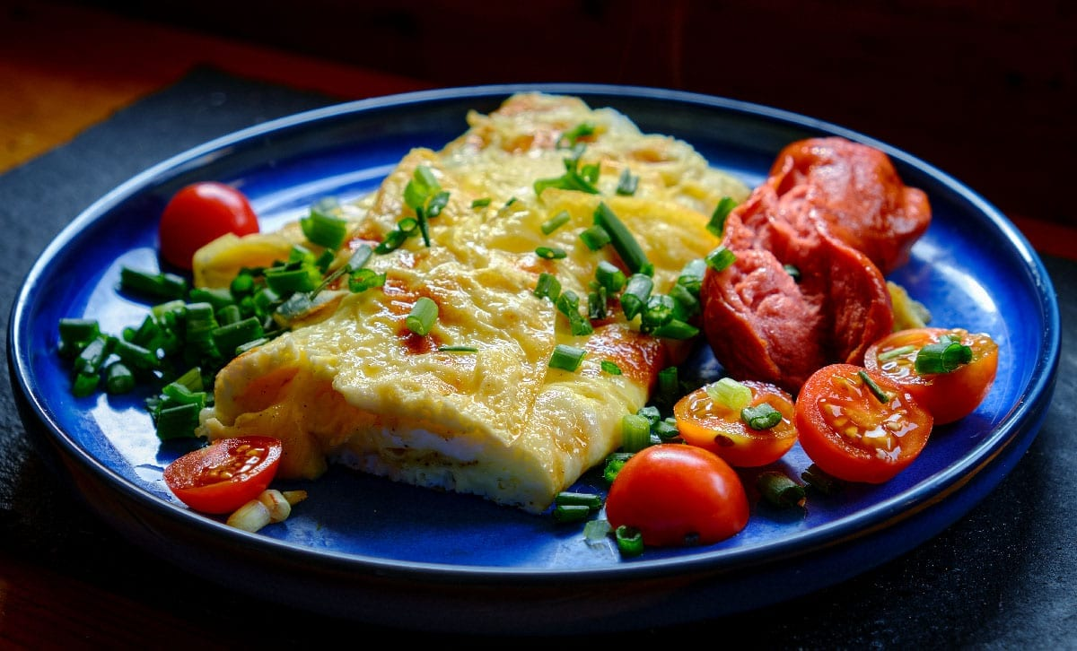 Omelette,With,Tomatoes,,Green,Onion,On,Blue,Plate.