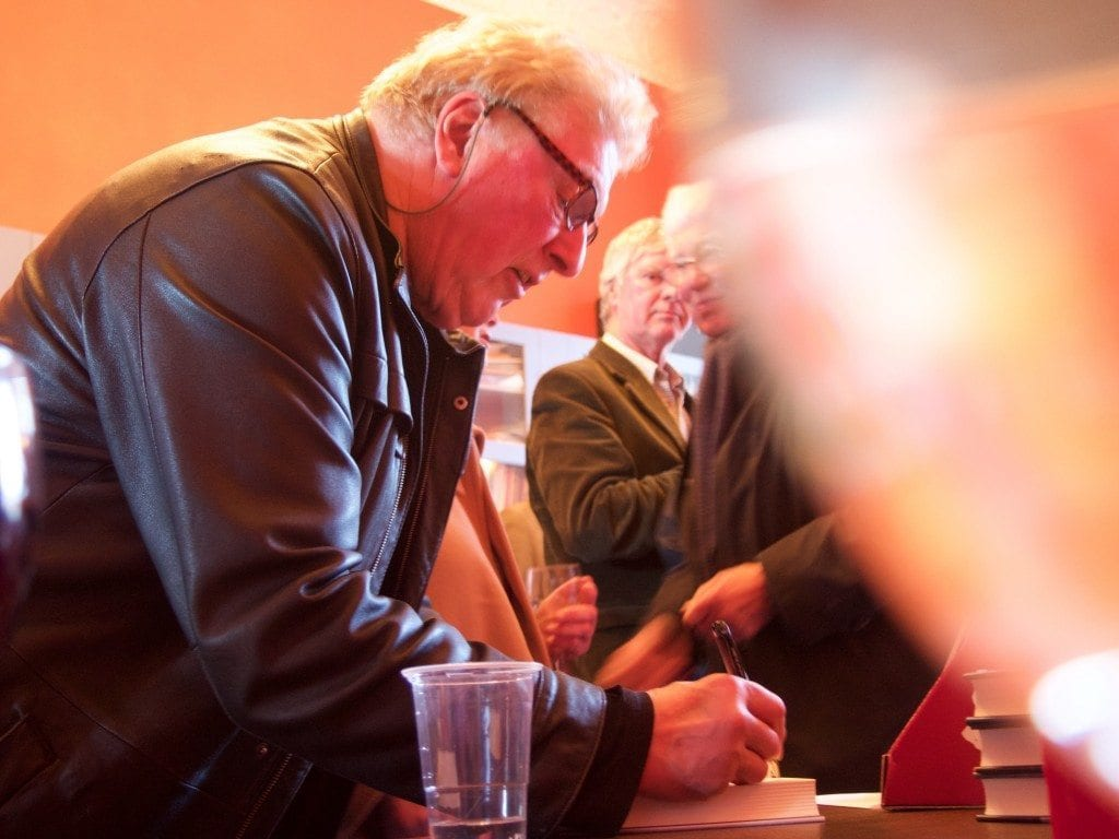 Dick Benson-Gyles signing copies of his book